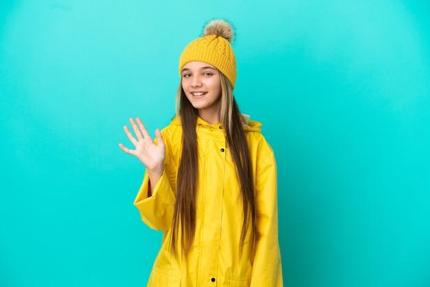 Menina vestindo um casaco à prova de chuva sobre um fundo azul isolado saudando com a mão com uma expressão feliz