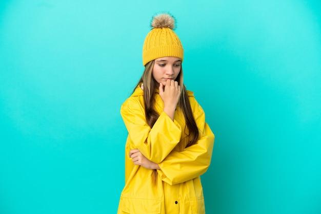 Menina vestindo um casaco à prova de chuva sobre um fundo azul isolado, tendo dúvidas