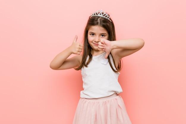 Menina vestindo um olhar de princesa mostrando os polegares para cima e os polegares para baixo, difícil escolher