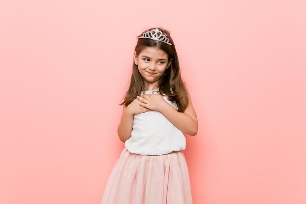 Menina vestindo uma aparência de princesa tem expressão amigável, pressionando a palma da mão no peito