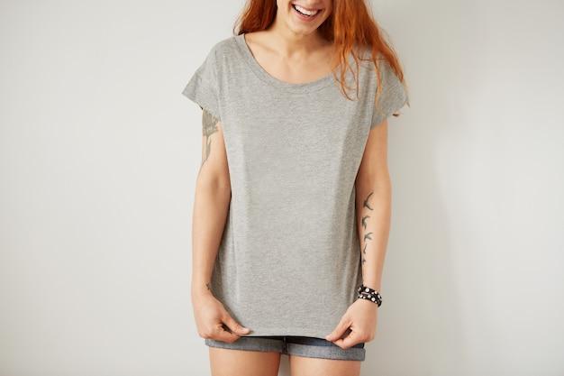 Menina vestindo uma camiseta cinza em branco em pé na parede branca
