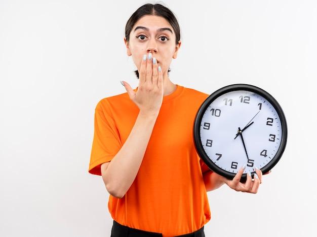 Menina vestindo uma camiseta laranja segurando um relógio de parede em choque cobrindo a boca com a mão em pé sobre uma parede branca