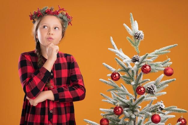 Menina vestindo uma guirlanda de natal em uma camisa xadrez, parecendo perplexa ao lado de uma árvore de natal sobre um muro laranja