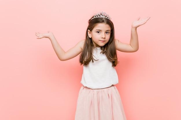 Menina vestindo uma princesa parece duvidar e encolher os ombros os ombros em gesto de questionamento.