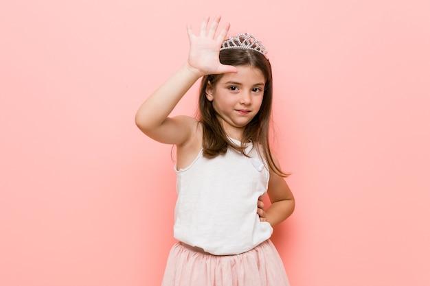 Menina vestindo uma princesa parece sorrindo alegre mostrando o número cinco com os dedos.