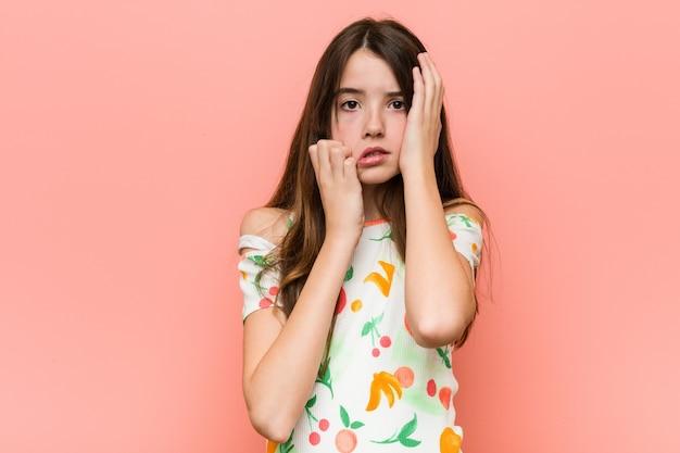 Menina vestindo uma roupa de verão contra uma parede vermelha, chorando e chorando desconsoladamente.