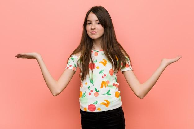 Menina vestindo uma roupa de verão contra uma parede vermelha faz escala com os braços, sente-se feliz e confiante.