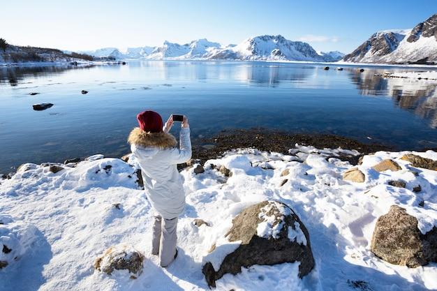 Menina viaja pelas ilhas lofoten e tira fotos para a câmera. bela paisagem norueguesa. noruega