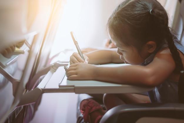 Menina viajando de avião e passar o tempo desenhando e lendo um livro durante o vôo