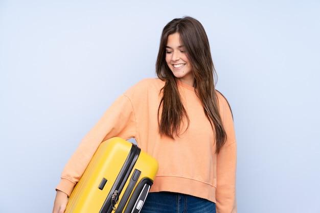 Menina viajante adolescente sobre parede azul