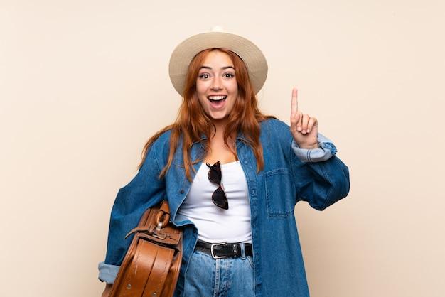 Menina viajante redhead com mala de viagem apontando para cima uma grande idéia