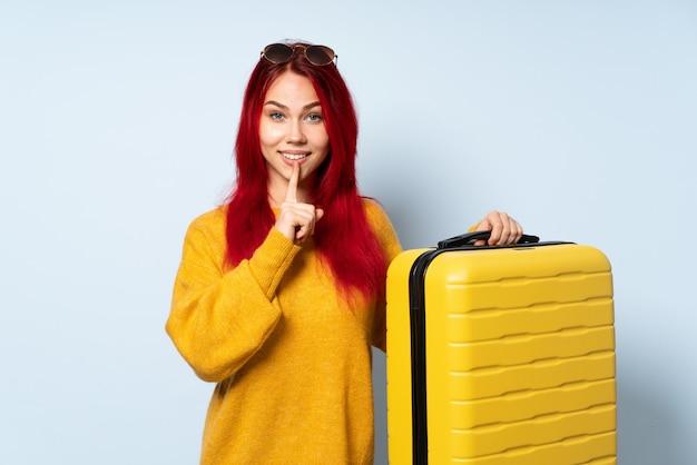 Menina viajante segurando uma mala isolada em azul, mostrando um sinal de gesto de silêncio colocando o dedo na boca