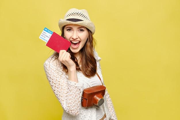 Menina viajante sorri e detém um passaporte com passagens aéreas e uma câmera vintage.