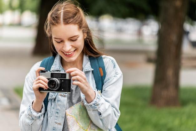 Menina viajante sorridente e câmera retro