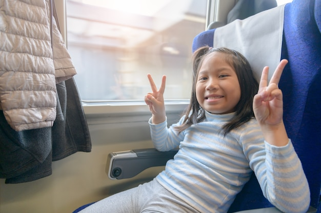Menina viajante sorriso e sente-se no trem
