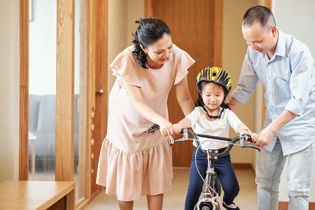 Menina vietnamita andando de bicicleta no corredor do apartamento com os pais ajudando-a a se equilibrar sobre duas rodas