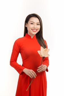 Menina vietnamita com um vestido vermelho ao dai na mão, flor de lótus. rosto feliz e sorridente