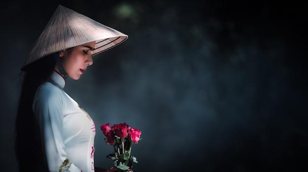Menina vietnamita em um vestido branco, usando um chapéu e as rosas vermelhas em mãos dadas