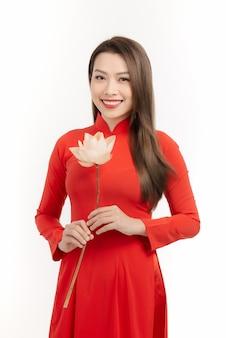 Menina vietnamita segurando uma flor de lótus. o ao dai é o traje tradicional da mulher vietnamita