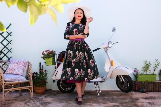 Menina vintage ao lado da motocicleta