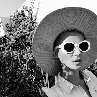 Menina vintage em acessórios de moda chapéu e óculos de sol na localização da planta praia retro clima