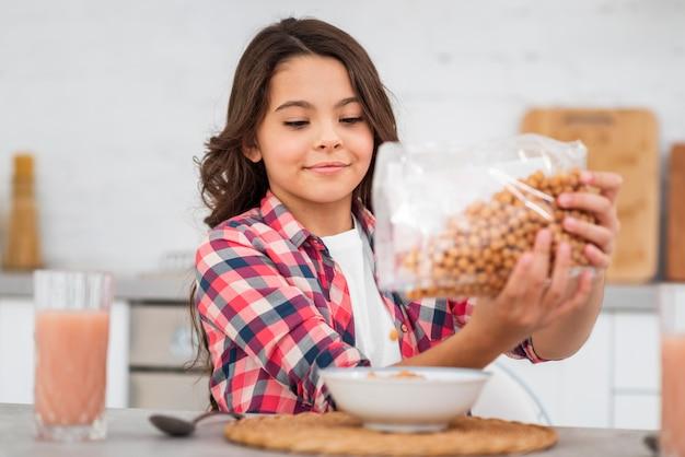 Menina vista frontal, preparando o café da manhã