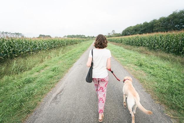 Menina vista por trás andando por uma estrada e carregando um cachorro na coleira