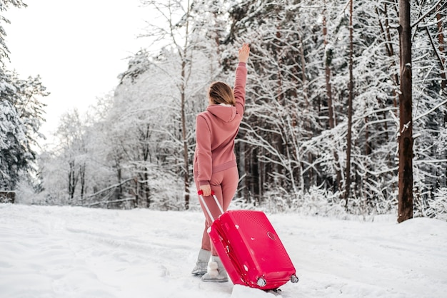 Menina vota na floresta por um carro quebrado. floresta de inverno, geada e neve.