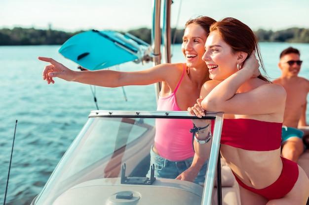 Meninas a bordo. vista lateral de duas lindas garotas com roupas de verão brilhantes, de pé ao volante de um barco de recreio