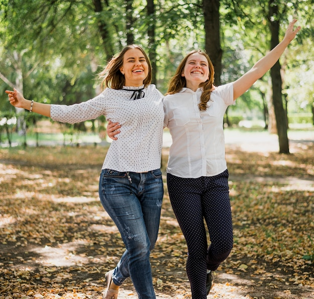 Meninas, abraçando e caminhando juntos