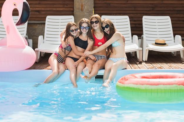 Meninas, abraçando, um ao outro, em, piscina