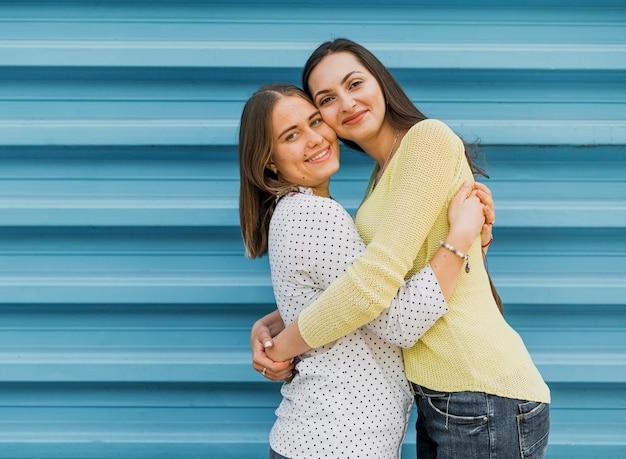 Meninas adolescente abraçando e olhando para a câmera