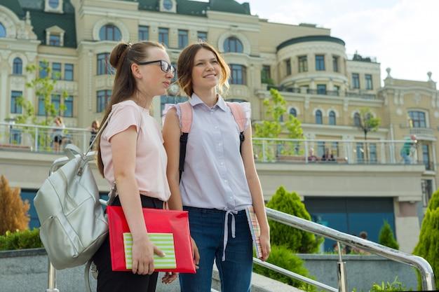 Meninas adolescentes com mochilas e livros escolares vão à escola.
