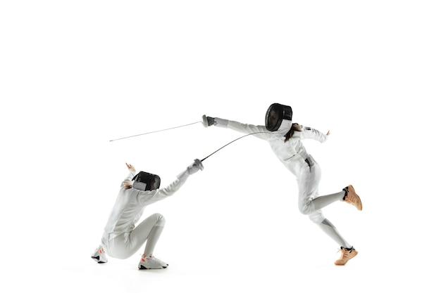Meninas adolescentes em trajes de esgrima com espadas nas mãos, isoladas no fundo branco do estúdio. jovens modelos femininos praticando e treinando em movimento, ação. copyspace. esporte, juventude, estilo de vida saudável.
