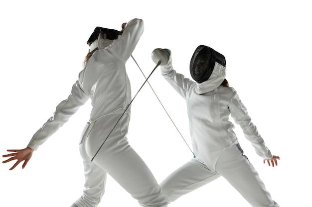 Meninas adolescentes em trajes de esgrima com espadas nas mãos, isoladas no fundo branco do estúdio. jovens modelos femininos praticando e treinando em movimento, ação. copyspace.
