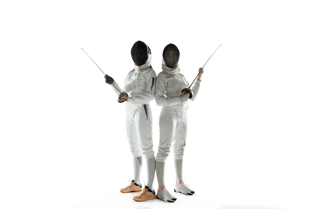 Meninas adolescentes em trajes de esgrima com espadas nas mãos, isoladas no fundo branco do estúdio. jovens modelos femininos treinando, posando de confiança. copyspace. esporte, juventude, estilo de vida saudável, movimento, ação.