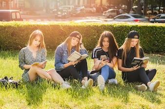 Meninas adolescentes, leitura, livros, e, usando, smartphone