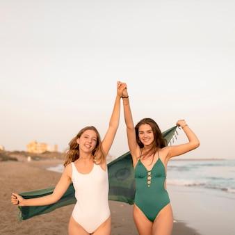 Meninas adolescentes, segurando, cada, outro, mão, desfrutando, em, praia