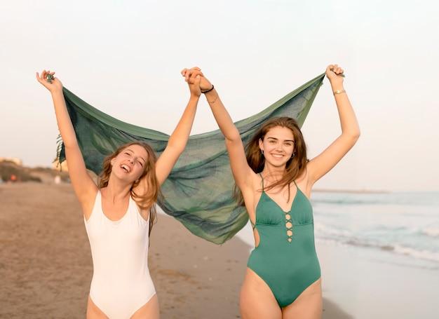 Meninas adolescentes, segurando, echarpe, e, cada, outro, mão, desfrutando, em, praia