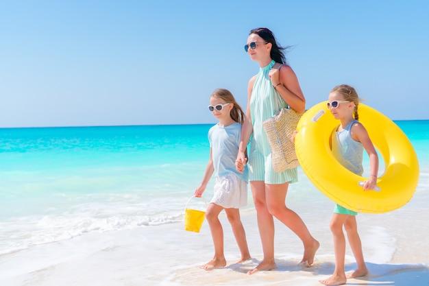 Meninas adoráveis e mãe nova na praia branca. vista para a família e o oceano