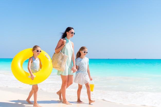 Meninas adoráveis e mãe nova na praia branca.