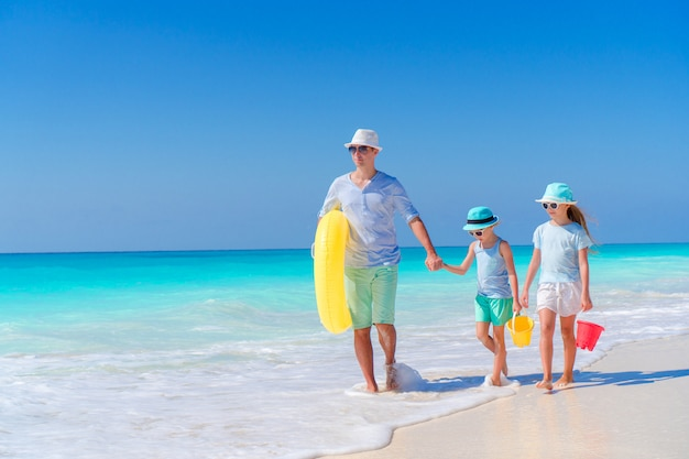 Meninas adoráveis e pai novo na praia branca. vista para a família e o oceano