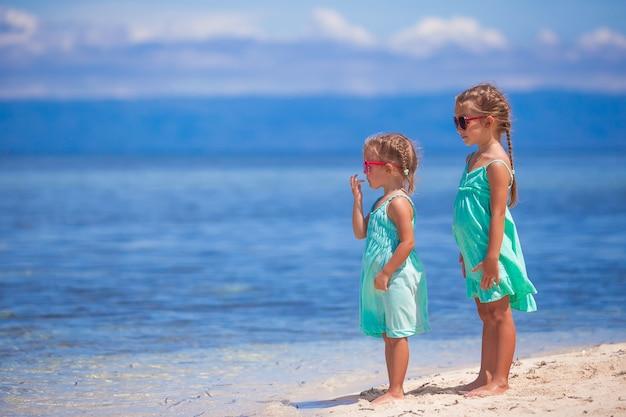 Meninas adoráveis em vestido turquesa na praia branca olham para o mar