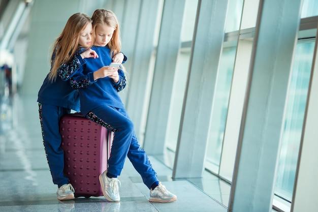 Meninas adoráveis no aeroporto perto da grande janela