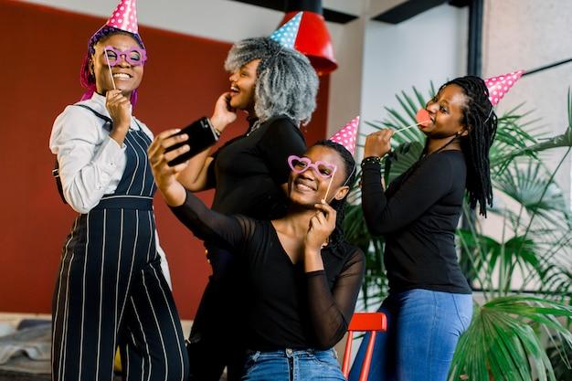 Meninas afro-americanas comemoram o aniversário de seu amigo, feliz, riem e fazendo selfi