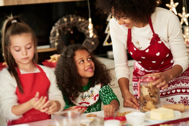 Meninas ajudando a mãe a fazer biscoitos para o natal
