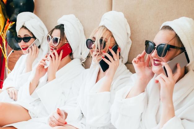 Meninas alegres do spa falando em smartphones. estilo de vida de lazer urbano das mulheres. vestidos com óculos de sol, roupões de banho e toalha turbante.