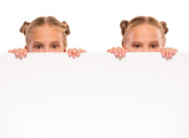 Meninas alegres dos gêmeos com uma placa branca.