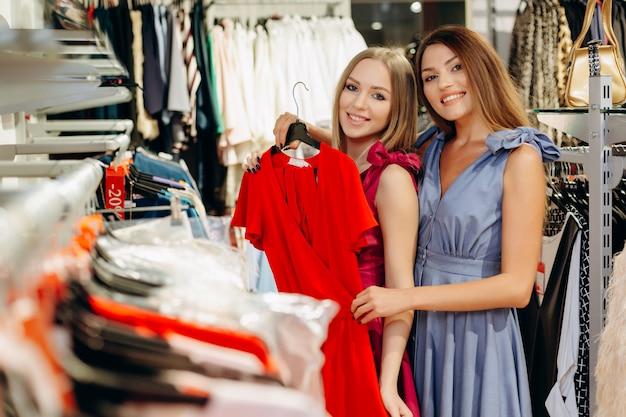 Meninas alegres e sorridentes olham para o vestido vermelho perto do estande.