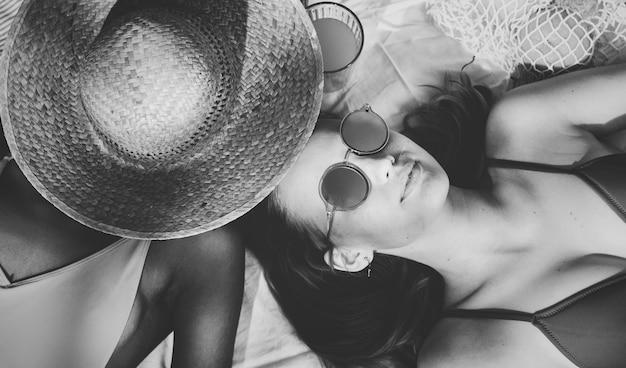 Meninas alegres em bronzeamento suntanning juntos